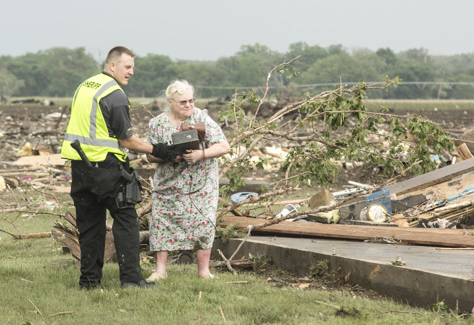 Photo - Ruth Labenz is assisted to safety by a Stanton County Sherriff's officer after her home was destroyed in the town of Pilger, Neb. Monday, June 16, 2014. At least one person is dead and at least 16 more are in critical condition after two massive tornadoes swept through northeast Nebraska on Monday. (AP Photo/Mark 'Storm' Farnik)