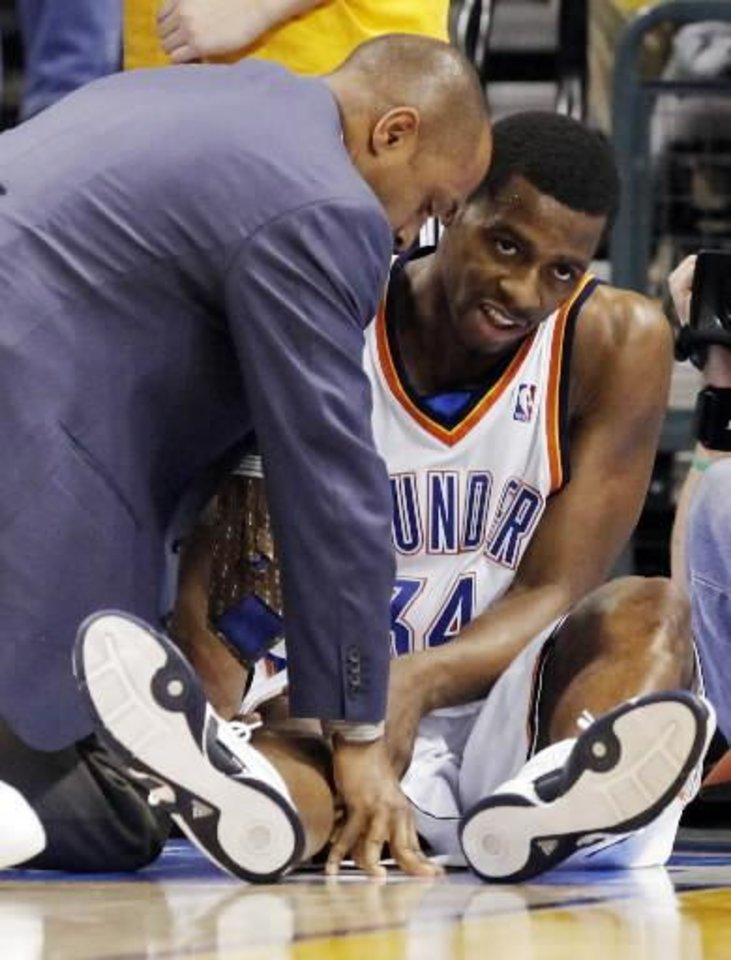 Photo - Oklahoma City's  Desmond  Mason has his leg examined after being injured in the third quarter of the NBA basketball game between the Oklahoma City Thunder and the Memphis Grizzlies at the Ford Center in Oklahoma City, Wednesday, January 28, 2009. BY NATE BILLINGS