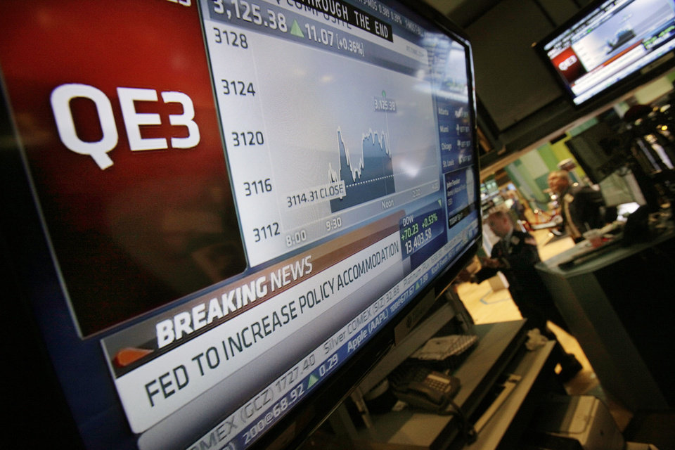 Photo -   The rate decision of the Federal Reserve is announced on a television screen on the floor of the New York Stock Exchange Thursday, Sept. 13, 2012. The Federal Reserve unleashed a series of aggressive actions Thursday intended to stimulate the still-weak economy by making it cheaper for consumers and businesses to borrow and spend. (AP Photo/Richard Drew)