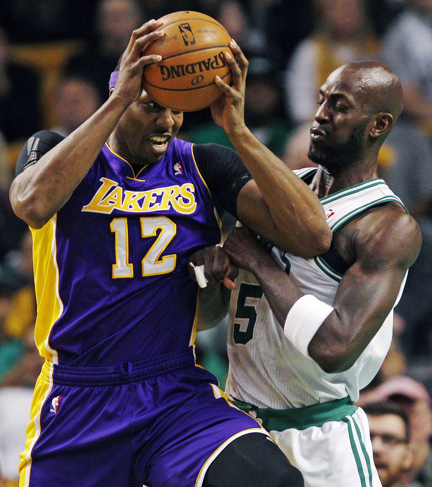 Los Angeles Lakers center Dwight Howard (12) tries to break free from Boston Celtics forward Kevin Garnett (5) on a drive to the basket during the first quarter of an NBA basketball game in Boston, Thursday, Feb. 7, 2013. (AP Photo/Charles Krupa)