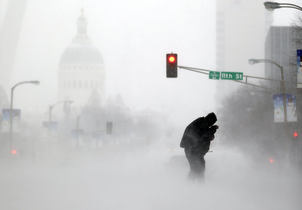Photo - A person struggles to cross a street in blowing and falling snow Sunday, Jan. 5, 2014, in St. Louis. Snow that began in parts of Missouri Saturday night picked up intensity after dawn Sunday with several inches of snow on the ground by midmorning and more on the way. (AP Photo/Jeff Roberson)