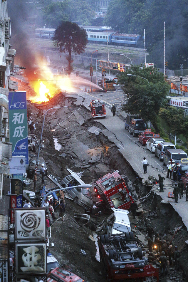 Photo - Vehicles are left lie in a destroyed street as part of the street is burning with flame following multiple explosions from an underground gas leak in Kaohsiung, Taiwan, early Friday, Aug. 1, 2014. A massive gas leakage early Friday caused five explosions that killed scores of people and injured over 200 in the southern Taiwan port city of Kaohsiung. (AP Photo) TAIWAN OUT