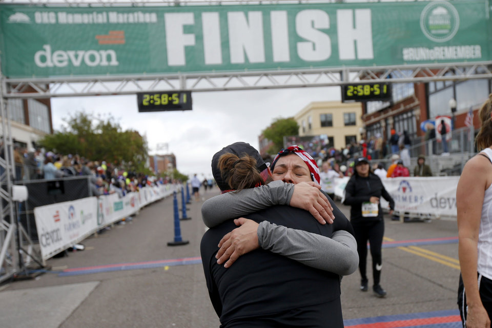 Photo -  Anna Carroll, back, hugs Lisa Baker after they finished the half marathon on Sunday. [PHOTO BY BRYAN TERRY, THE OKLAHOMAN]