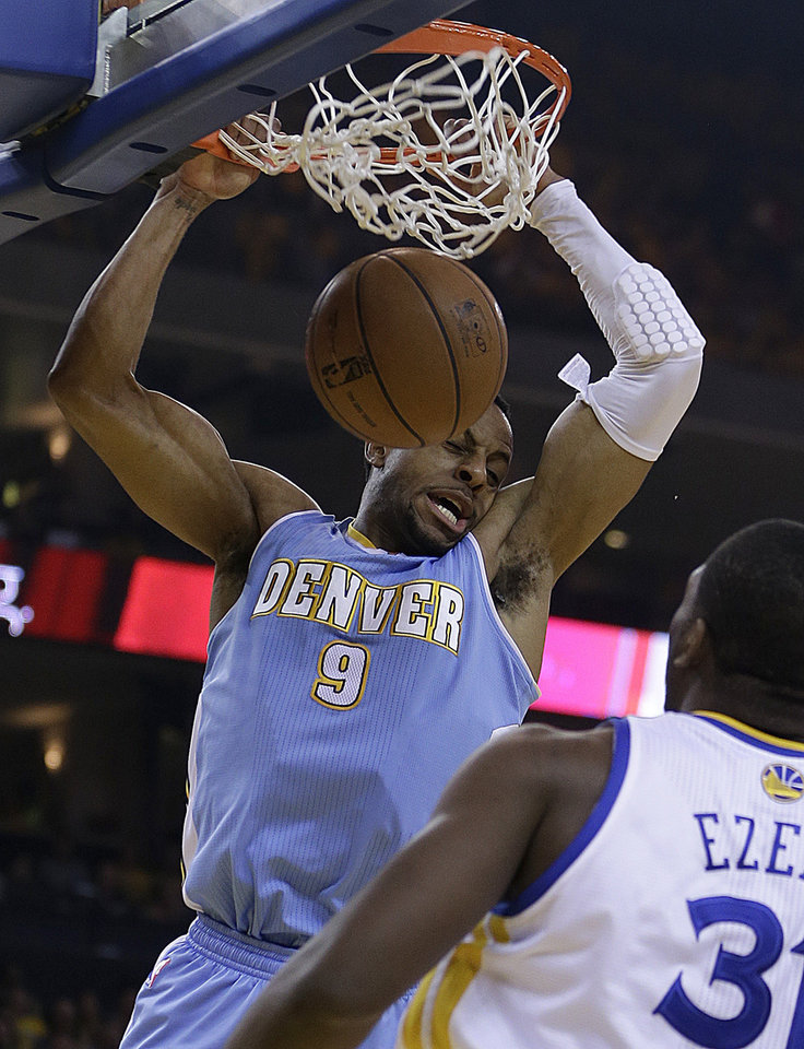 Photo - Denver Nuggets' Andre Iguodala (9) scores against Golden State Warriors' Festus Ezeli during the first half of Game 3 in a first-round NBA basketball playoff series on Friday, April 26, 2013, in Oakland, Calif. (AP Photo/Ben Margot)