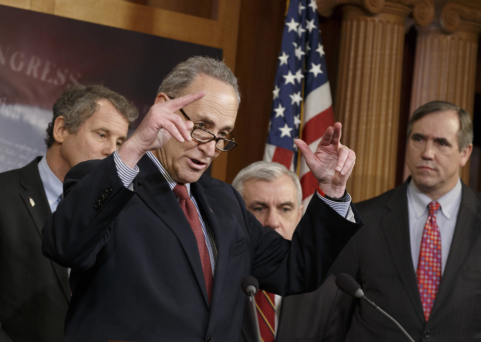 Photo - Sen. Charles Schumer, D-N.Y., second from left, gestures during a news conference on Capitol Hill in Washington, Tuesday, Jan. 7, 2014, after legislation to renew jobless benefits for the long-term unemployed unexpectedly cleared an initial Senate hurdle. From left are, Sen. Sherrod Brown, D-Ohio, Schumer, Sen. Jack Reed, D-R.I., and Sen. Jeff Merkley, D-Ore. The vote was 60-37 to limit debate on the legislation, with a half-dozen Republicans siding with the Democrats on the test vote. Sen. Jack Reed, D-R.I., along with Republican Sen. Dean Heller of Nevada, led the effort to reauthorize the benefits for three months which expired on Dec. 28. (AP Photo/J. Scott Applewhite)