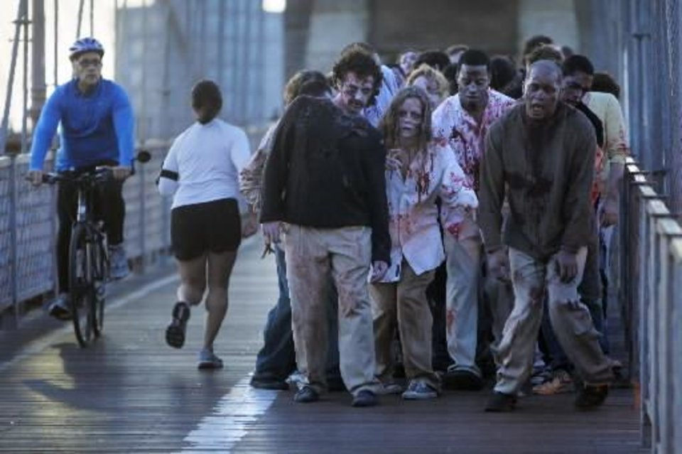 A bicyclist and jogger pass a group of zombies posing for pictures on the Brooklyn Bridge in New York, Tuesday, Oct. 26, 2010. The stunt was part of a campaign in 26 cities worldwide promoting the Halloween premiere of the AMC television series
