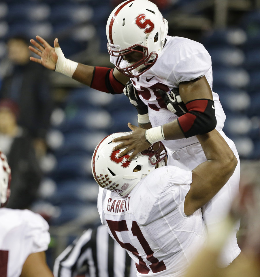 Photo - Stanford's Barry Sanders is lifted up by Joshua Garnett after Sanders 22-yard touchdown run against Washington State in the second half of an NCAA college football game Saturday, Sept. 28, 2013, in Seattle. Stanford won 55-17. (AP Photo/Elaine Thompson) ORG XMIT: WAET119