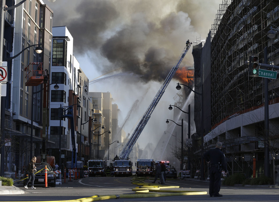Photo - Firefighters battle a fire burning in San Francisco, Tuesday, March 11, 2014. The major fire burning in San Francisco's Mission Bay neighborhood sent an enormous plume of black smoke high into the sky. There were no initial reports of injuries. The four-alarm fire that began about 5 p.m. was ravaging a high-rise building under construction and moving down a block. (AP Photo/Jeff Chiu)