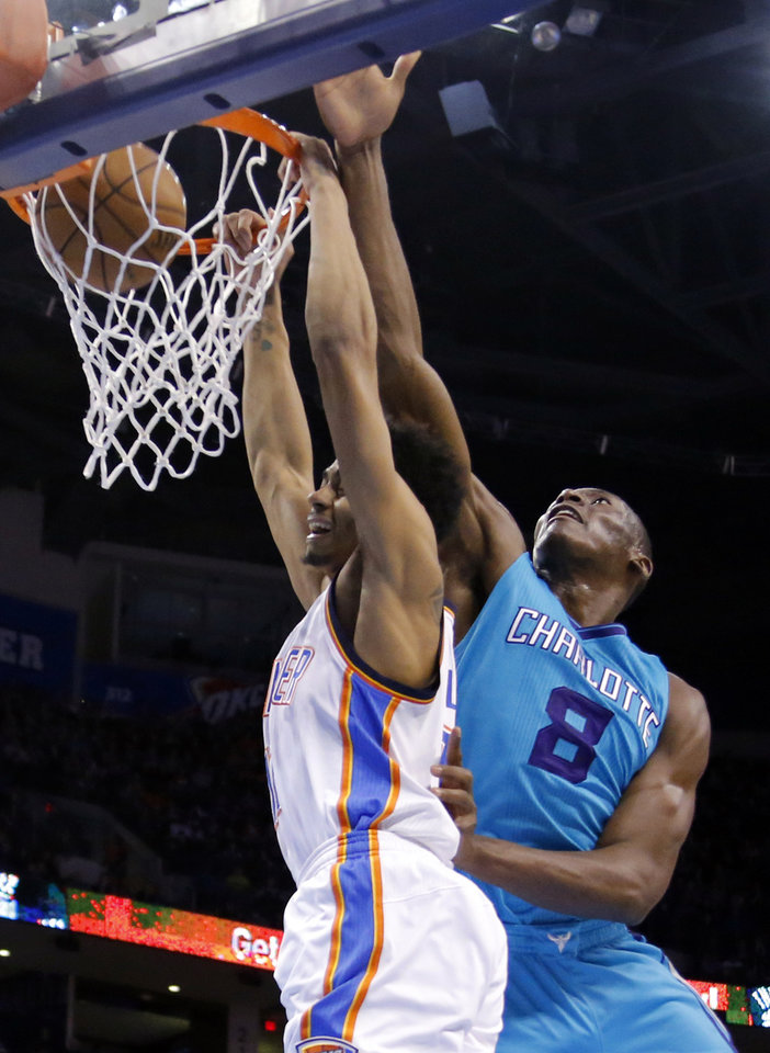 Photo - Oklahoma City's Jeremy Lamb (11) dunks as Charlotte's Bismack Biyombo (8) defends during the NBA basketball game between the Oklahoma City Thunder and the Charlotte Hornets at the Chesapeake Energy Arena in Oklahoma City, Friday, Dec. 26, 2014. Photo by Sarah Phipps, The Oklahoman