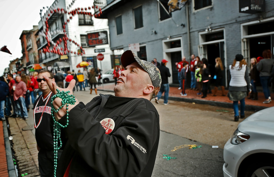 Photo - Sooner fan Derrik Hogan catches beads thrown from the balconies on Bourbon Street before the start of the NCAA football BCS Sugar Bowl game between the University of Oklahoma Sooners (OU) and the University of Alabama Crimson Tide (UA) at the Superdome in New Orleans, La., Thursday, Jan. 2, 2014.  .Photo by Chris Landsberger, The Oklahoman