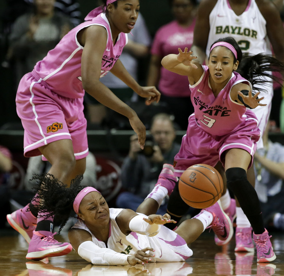 Photo - Baylor Bears' Odyssey Sims (0) passes the ball after winning control of it on a scramble on the floor against Oklahoma State 's LaShawn Jones, left, and Tiffany Bias (3) in the first half of an NCAA college basketball game on Sunday, Feb. 9, 2014, in Waco, Texas. (AP Photo/Tony Gutierrez)