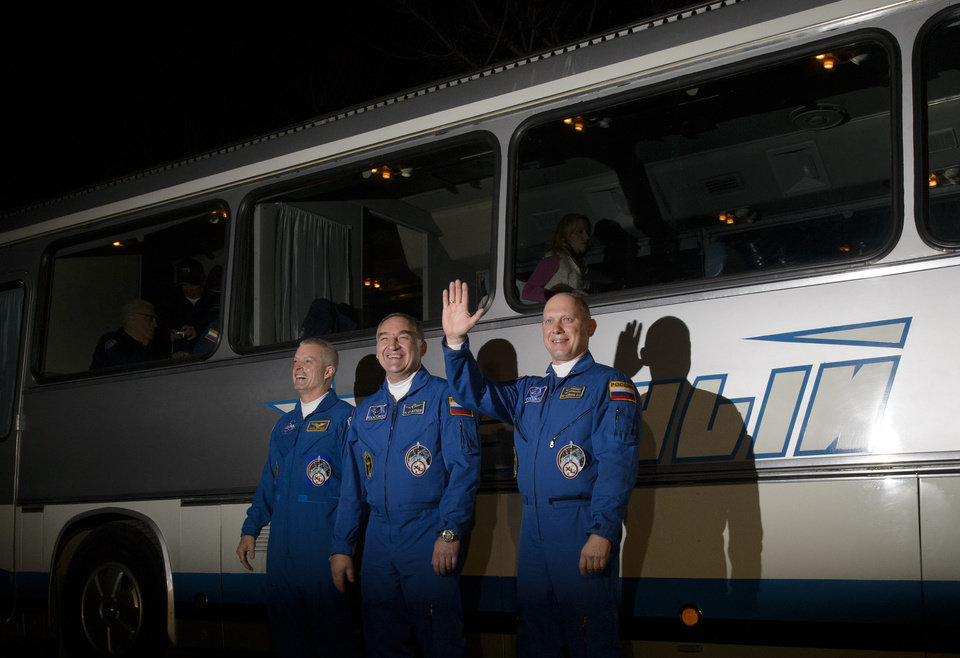 Photo - In this image released by NASA, from left, Expedition 39 flight engineer Steven Swanson of NASA, Soyuz commander Aleksander Skvortsov, of the Russian Federal Space Agency (Roscosmos), and flight engineer Oleg Artemyev of Roscosmos, wave as they depart the Cosmonaut Hotel Tuesday, March 25, 2014, in Baikonur, Kazakhstan. The mission is set to launch March 26 from the Baikonur Cosmodrome.  (AP Photo/NASA, Joel Kowsky) MANDATORY CREDIT