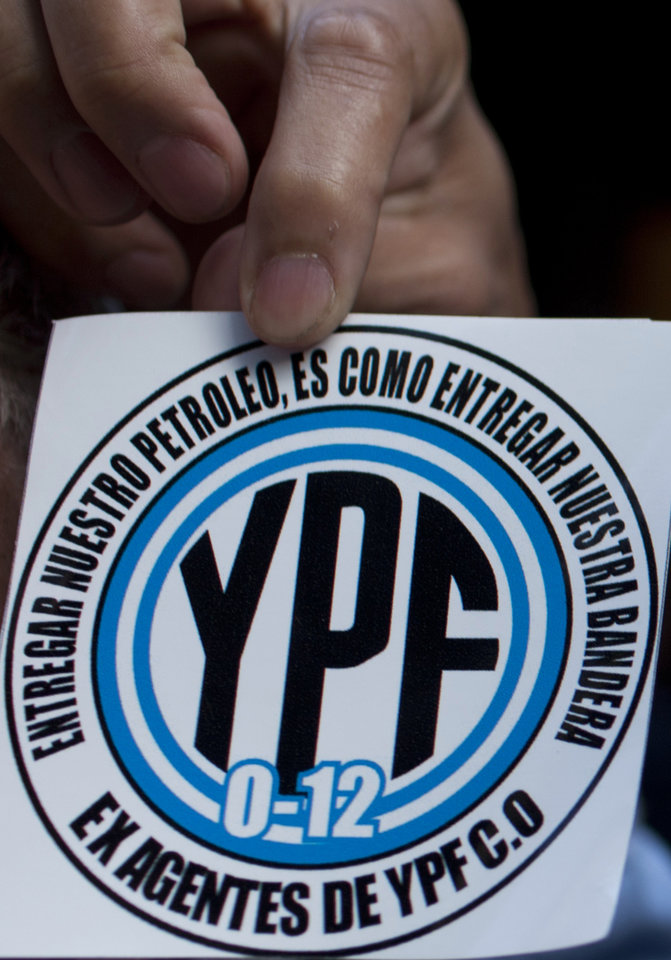"A man shows a sticker that reads in Spanish ""YPF. To hand over our oil, is like handing over our flag"" outside Congress as lawmakers debate the YPF bill on the expropriation of the oil company in Buenos Aires, Argentina, Wednesday, May 2, 2012. President Cristina Fernandez, who pushed forward a bill to renationalize the country's largest oil company, said the legislation put to congress would give Argentina a majority stake in oil and gas company YPF by taking control of 51 percent of its shares currently held by Spain's Repsol. (AP Photo/Natacha Pisarenko)"