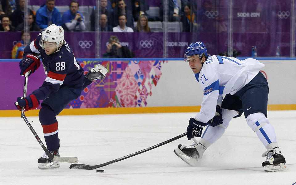Photo - USA forward Patrick Kane breaks his stick while taking a shot on goal as Finland forward Leo Komarov defends during the second period of the men's bronze medal ice hockey game at the 2014 Winter Olympics, Saturday, Feb. 22, 2014, in Sochi, Russia. Komarov was called for slashing on the play and the USA was awarded a penalty shot. (AP Photo/Petr David Josek)
