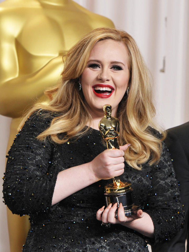 Photo - Adele poses with her award for best original song for