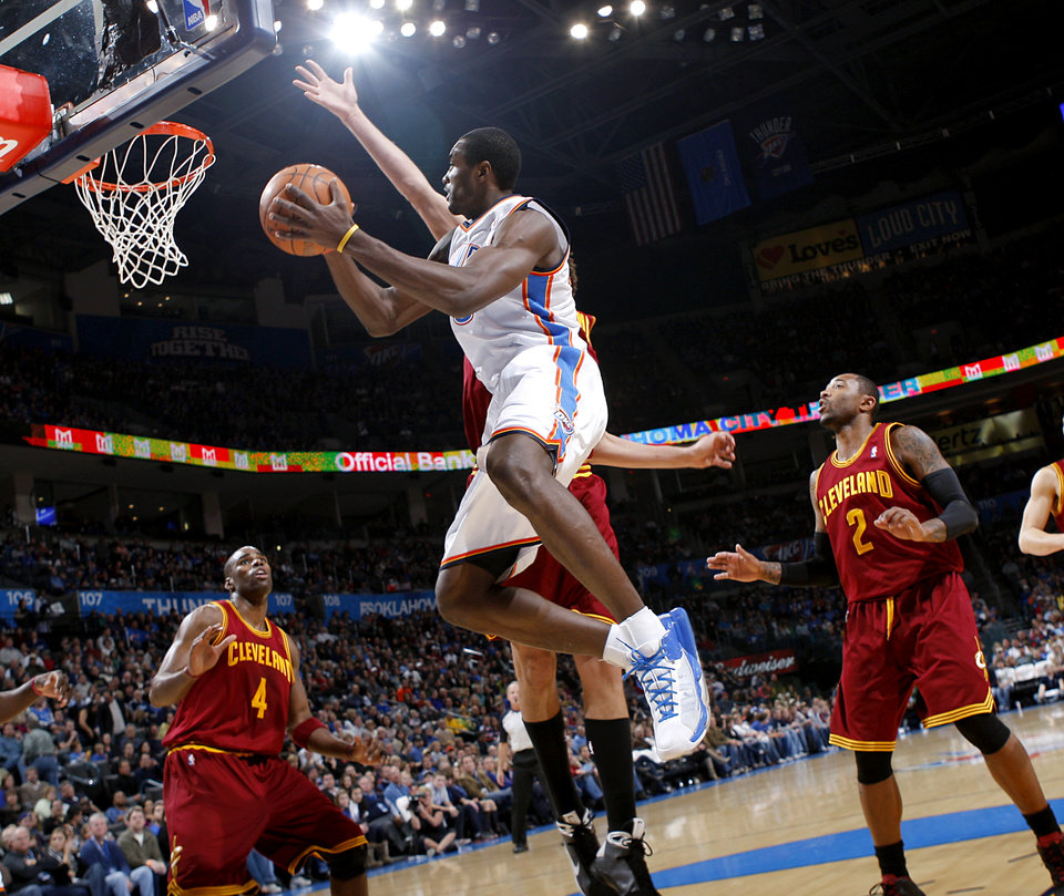 Photo - Oklahoma City's Serge Ibaka puts up a shot in front of Cleveland's defense during the first half of their NBA basketball game at the OKC Arena in Oklahoma City on Sunday, Dec. 12, 2010. Photo by John Clanton, The Oklahoman