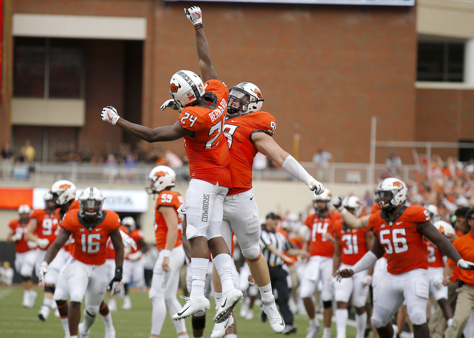 Photo - Oklahoma State's Jarrick Bernard (24) and Brendon Evers (98) celebrate an OSU blocked punt and touchdown in the third quarter during a college football game between the Oklahoma State Cowboys (OSU) and the Boise State Broncos at Boone Pickens Stadium in Stillwater, Okla., Saturday, Sept. 15, 2018. OSU won 44-21. Photo by Sarah Phipps, The Oklahoman