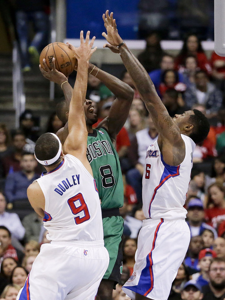 Photo - Boston Celtics forward Jeff Green, middle tries to get a shot off between Los Angeles Clippers forward Jared Dudley, left, and center DeAndre Jordan during the first half of an NBA basketball game in Los Angeles, Wednesday, Jan. 8, 2014. (AP Photo/Chris Carlson)