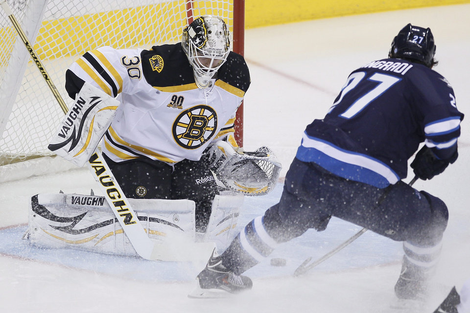 Photo - Boston Bruins goaltender Chad Johnson (30) saves a shot by Winnipeg Jets' Eric Tangradi (27) during the first period of an NHL hockey game Thursday, April 10, 2014, in Winnipeg, Manitoba. (AP Photo/The Canadian Press, John Woods)