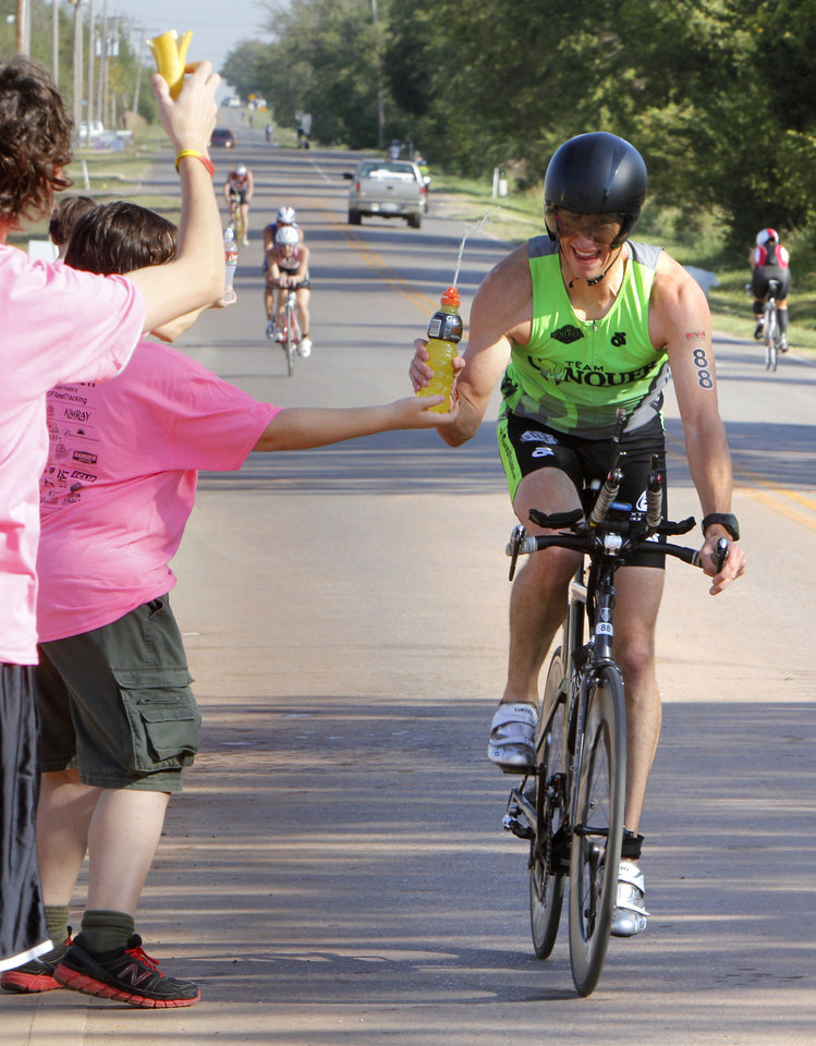 Phil Carlson takes a refreshment on the go from a volunteer in front of Deer Creek High School during the Redman Triathlon in Oklahoma City, OK, Saturday, September 22, 2012, By Paul Hellstern, The Oklahoman
