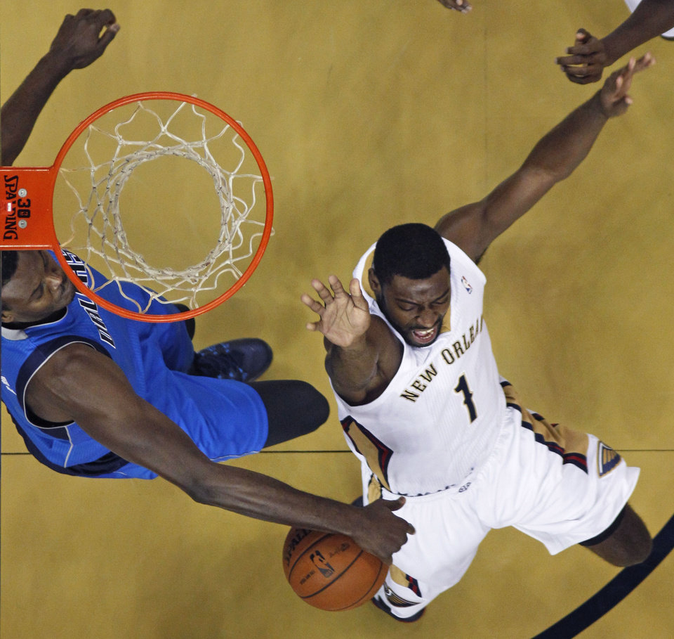 Photo - New Orleans Pelicans point guard Tyreke Evans (1) is stripped of the ball by Dallas Mavericks center Samuel Dalembert, left, as he drives to the basket in the first half of an NBA basketball game in New Orleans, Wednesday, Dec. 4, 2013. (AP Photo/Gerald Herbert)