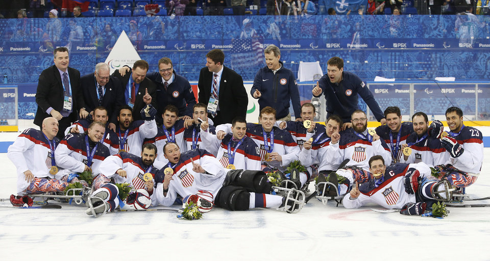 Photo - United States players and team officials pose for a team photo after they won gold medals at ice sledge hockey match between United States and Russia at the 2014 Winter Paralympics in Sochi, Russia, Saturday, March 15, 2014. United States won 1-0. (AP Photo/Pavel Golovkin)