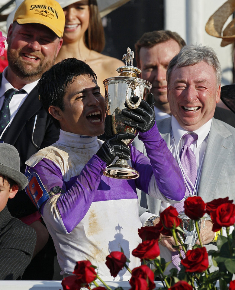 Jockey Mario Gutierrez kisses the trophy after riding I'll Have Another to victory in the 138th Kentucky Derby horse race at Churchill Downs Saturday, May 5, 2012, in Louisville, Ky. J. Paul Reddam, the owner, is at right. (AP Photo/Mark Humphrey) ORG XMIT: DBY207