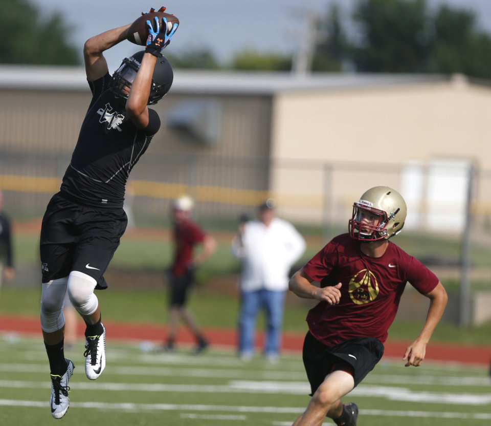 Photo - Westmoore's DeShawn Lookout catches a pass during a 7 on 7 tournament game at Westmoore High School in Moore, Okla.,  Saturday, June 28, 2014. Photo by Sarah Phipps, The Oklahoman