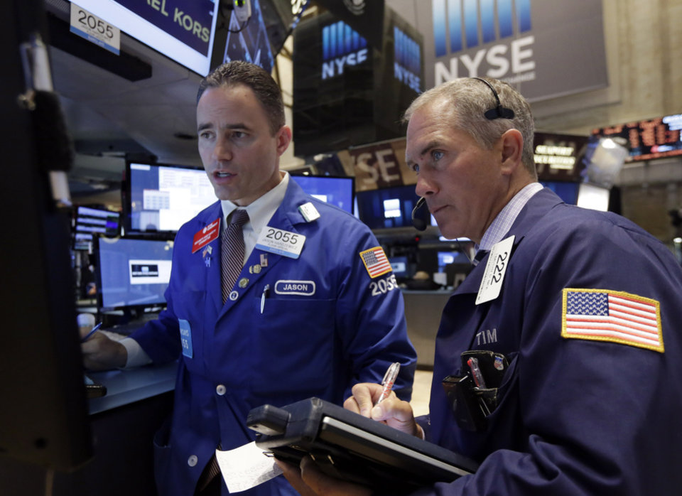 Photo - Trader Timothy Nick, right, and specialist Jason Hardzewicz work on the floor of the New York Stock Exchange Monday, June 23, 2014. Stocks are edging lower in early trading after indexed closed last week at record highs. (AP Photo/Richard Drew)