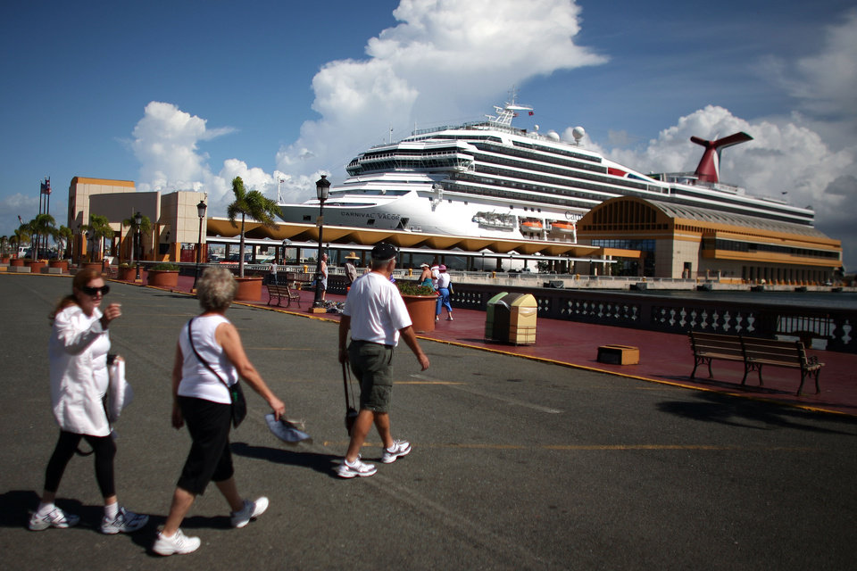 Photo -   In this Oct. 2, 2012 photo, tourists walk through a parking lot in front of a pier where a cruise ship is docked in Old San Juan, Puerto Rico. Trade groups say the flourishing cruise ship industry injects about $2 billion a year into the economies of the Caribbean, the world's No. 1 cruise destination, but critics complain that it produces relatively little local revenue because so many passengers dine, shop and purchase heavily marked-up shore excursions on the boats or splurge at international chain shops on the piers. (AP Photo/Ricardo Arduengo)