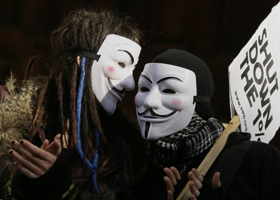 Demonstrators wear masks as they celebrate the anniversary of 'Occupy', outside St Paul's cathedral in London, Saturday, Oct. 13, 2012. Monday Oct. 15, marks the first anniversary of Occupy, the day when demonstrations and occupations took place in cities around the world. (AP Photo/Kirsty Wigglesworth)