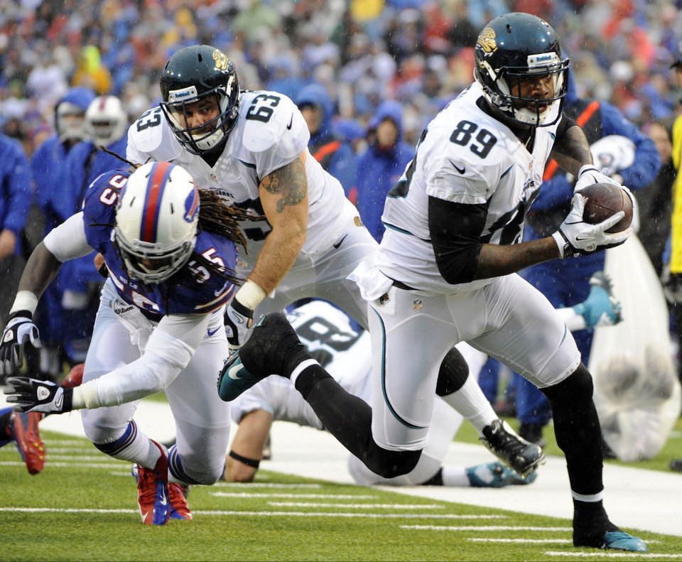 Photo - Jacksonville Jaguars tight end Marcedes Lewis (89) runs away from Buffalo Bills linebacker Kelvin Sheppard (55) during the first half of an NFL football game on Sunday, Dec. 2, 2012, in Orchard Park, N.Y. (AP Photo/Gary Wiepert)