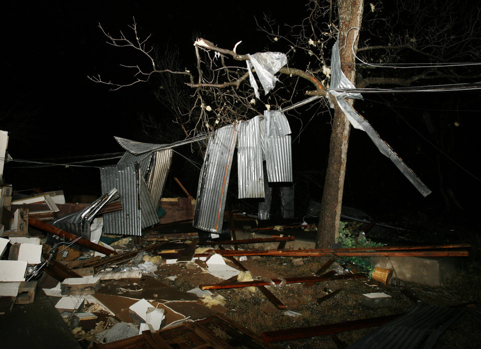 Photo - A metal roof rests of downed power lines behind a furniture store on Highway 70 after a tornado killed at least 8 people and destroyed much of the city of Lone Grove in southern Oklahoma on Tuesday, Feb. 10, 2009.   Photo by Steve Sisney, The Oklahoman