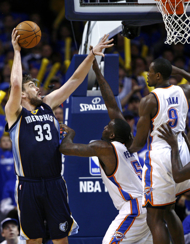 Photo -   Memphis Grizzlies center Marc Gasol, left, of Spain, shoots in front of Oklahoma City Thunder center Kendrick Perkins, center, and forward Serge Ibaka, right, of the Republic of the Congo, in the third quarter of Game 1 of a second-round NBA basketball playoff series in Oklahoma City, Sunday, May 1, 2011. (AP Photo/Alonzo Adams)