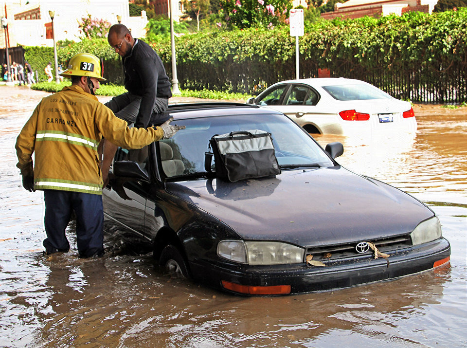 Photo - A Los Angeles firefighter helps a driver whose car became stranded on Sunset Boulevard after a 30-inch water main broke and sent water flooding down Sunset and onto the UCLA campus in the Westwood section of Los Angeles Tuesday, July 29, 2014. (AP Photo/Steve Gentry)