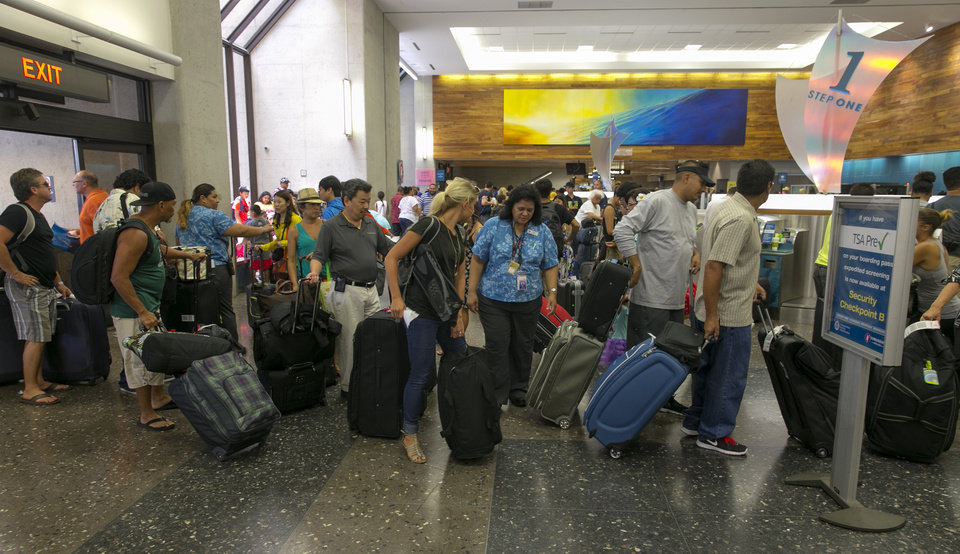 Crowds line up inside the departures terminal at the Honolulu International Airport in Honolulu on Thursday, Aug. 7, 2014. With Iselle, Hawaii is expected to take its first direct hurricane hit in 22 years. Tracking close behind it is Hurricane Julio. Hawaiian Airlines announced Thursday they are waiving change fees for passengers trying to leave before the hurricanes hit the islands. (AP Photo/Marco Garcia)