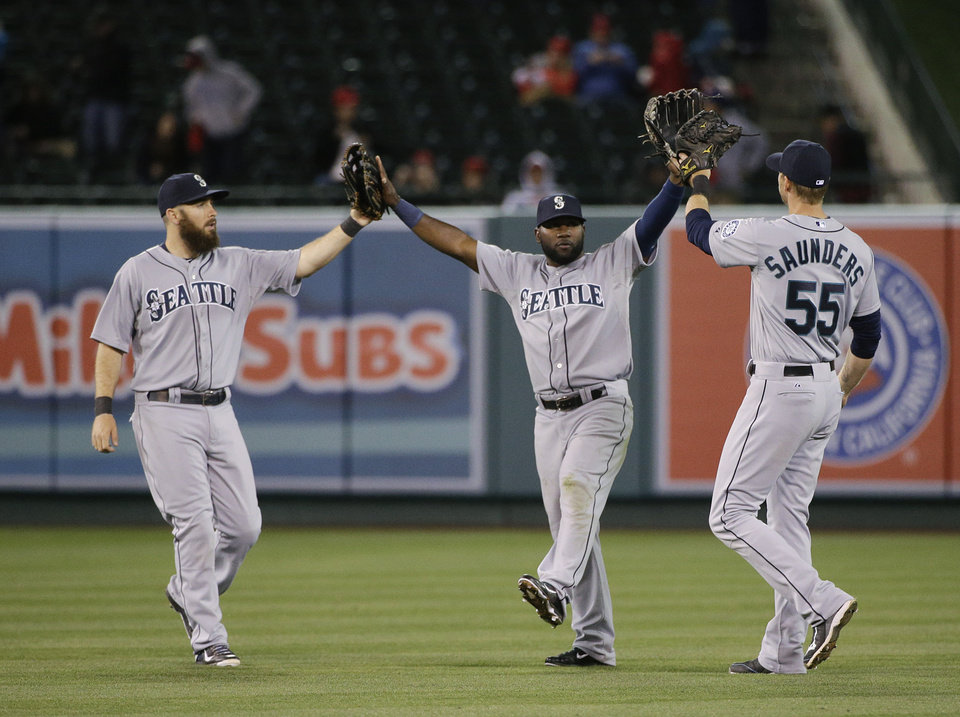 Photo - Seattle Mariners' Dustin Ackley, Abraham Almonte and Michael Saunders, from left, celebrate their team's 8-2 win against the Los Angeles Angels in a baseball game Wednesday, April 2, 2014, in Anaheim, Calif. (AP Photo/Jae C. Hong)