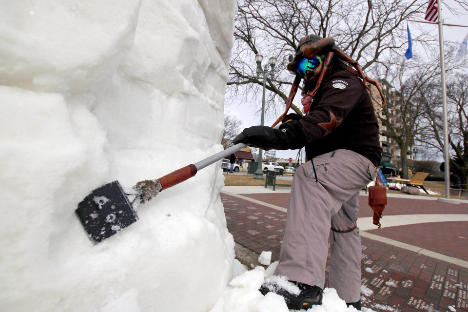 "Photo - In this Jan. 31. 2018 photo, Dusty Thune, from St. Paul, Minn., carves a snow block at the U.S. National Snow Sculpting Championship in Lake Geneva, Wis. Fifteen teams from 10 states have gathered in Wisconsin for the annual event. The Minnesota team, of which Thune is part, is creating a twisted President Donald Trump face in a suit called ""Peep,"" with the caption ""Tweet with a Twist."" The entries will be judged Saturday on creativity, technique and message. (AP Photo/Carrie Antlfinger)"