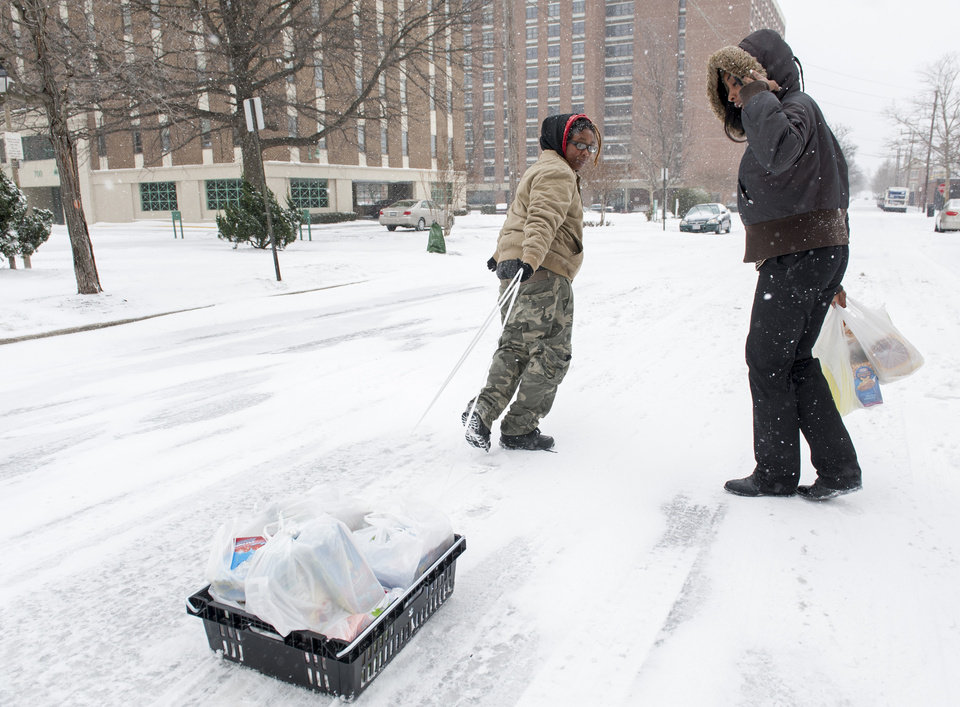 Photo - Shaquella Newby, 21, right, looks back as her partner Brittany Bigby, 25, pulls a make-shift sled full of groceries to their home, from a grocery store in Alexandria, Va., Monday, March 3, 2014. The National Weather Service has issued a Winter Storm Warning for the greater Washington Metropolitan region, prompting area schools and the federal government to close for the wintry weather. (AP Photo/Cliff Owen)