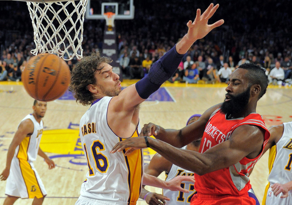 Photo -   Houston Rockets guard James Harden, right, passes the ball past Los Angeles Lakers forward Pau Gasol, of Spain, during the first half of their NBA basketball game, Sunday, Nov. 18, 2012, in Los Angeles. (AP Photo/Mark J. Terrill)