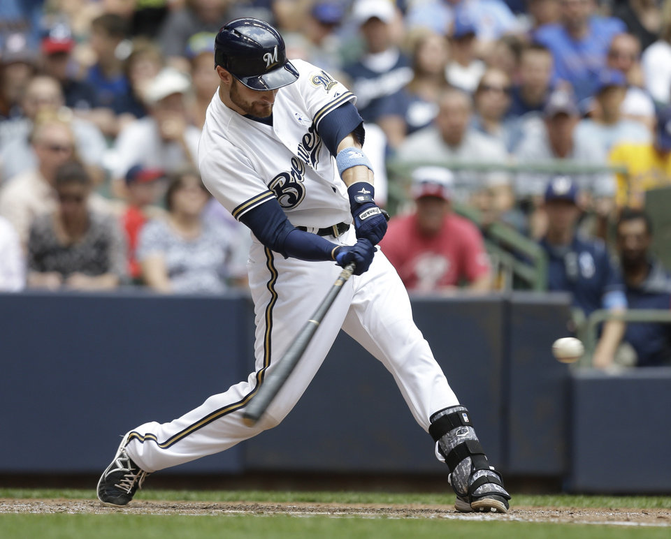 Photo - Milwaukee Brewers' Jonathan Lucroy hits a home run against the Cincinnati Reds during the fifth inning of a baseball game Sunday, June 15, 2014, in Milwaukee. (AP Photo/Jeffrey Phelps)