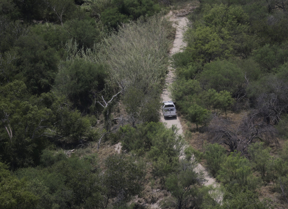 Photo - A Customs and Border Protection vehicle patrols on the Texas border near the Rio Grande, Thursday, July 24, 2014, in Mission, Texas. Texas is spending $1.3 million a week for a bigger DPS presence along the border. (AP Photo/Eric Gay, Pool)