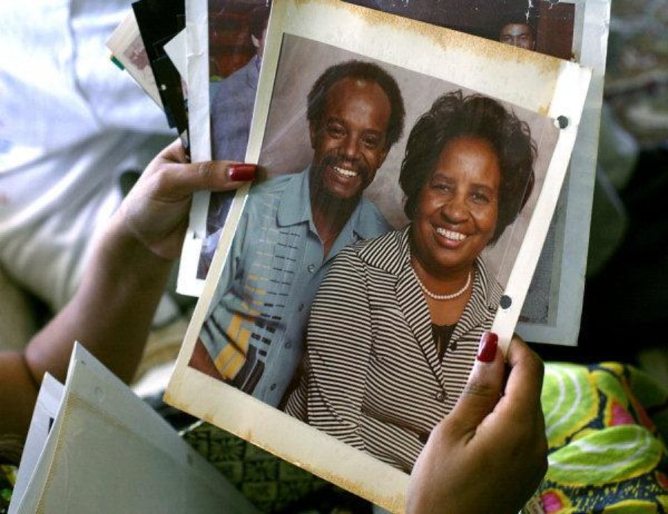 Photo - Chelle Luper Wilson, Clara Luper's youngest daughter, looks through pictures of her mother including this one of Clara Luper and her son Calvin Luper at Clara's home in Oklahoma City on Wednesday.   JOHN CLANTON - JOHN CLANTON