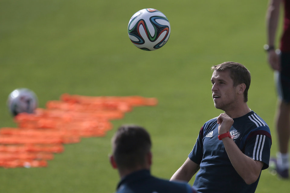 Photo - Dmitry Kombarov heads the ball during the Russian national soccer team's training session in Itu, Brazil, on Saturday, June 14, 2014. Russia will play in group H of the 2014 soccer World Cup. (AP Photo/Ivan Sekretarev)