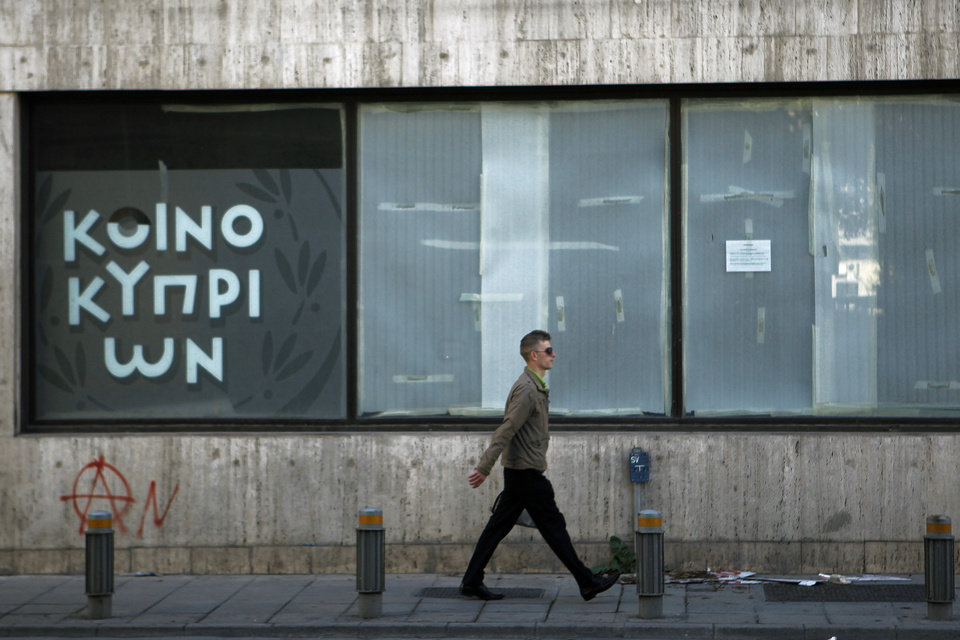 Photo - A man passes an empty closed branch of Bank of Cyprus in central capital Nicosia, Cyprus, Sunday, March 24, 2013. A top European official is leading a high-level meeting Sunday afternoon in a last-ditch effort to help Cyprus come up with a plan necessary for a 10 billion euro bailout loan that would save it from bankruptcy. (AP Photo/Petros Karadjias)