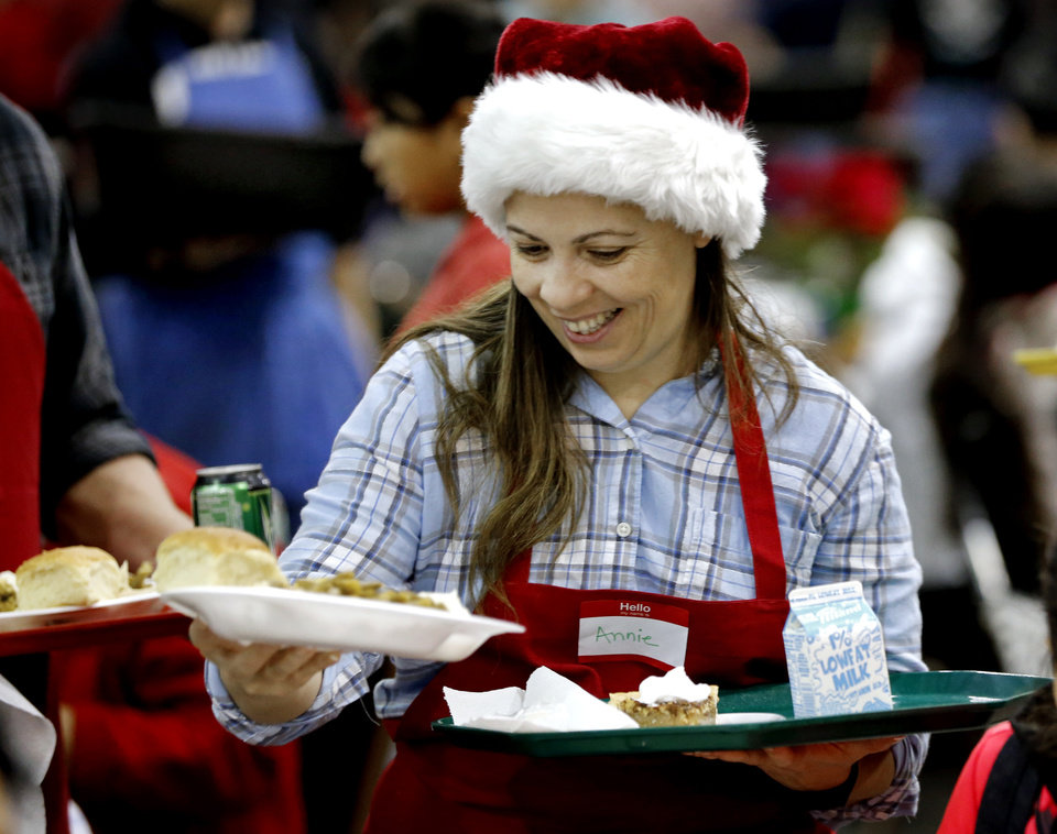Photo -  Annie Foote, a volunteer from Edmond, serves tables during the annual Red Andrews Christmas Dinner. [Photo by Steve Sisney, The Oklahoman]