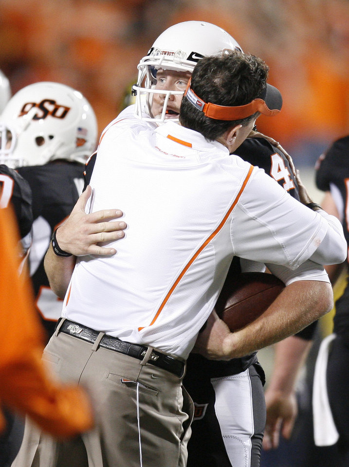 Photo - OSU's Brandon Weeden gets a hug after the college football game between Oklahoma State University (OSU) and the University of Colorado (CU) at Boone Pickens Stadium in Stillwater, Okla., Thursday, Nov. 19, 2009. Photo by Bryan Terry, The Oklahoman