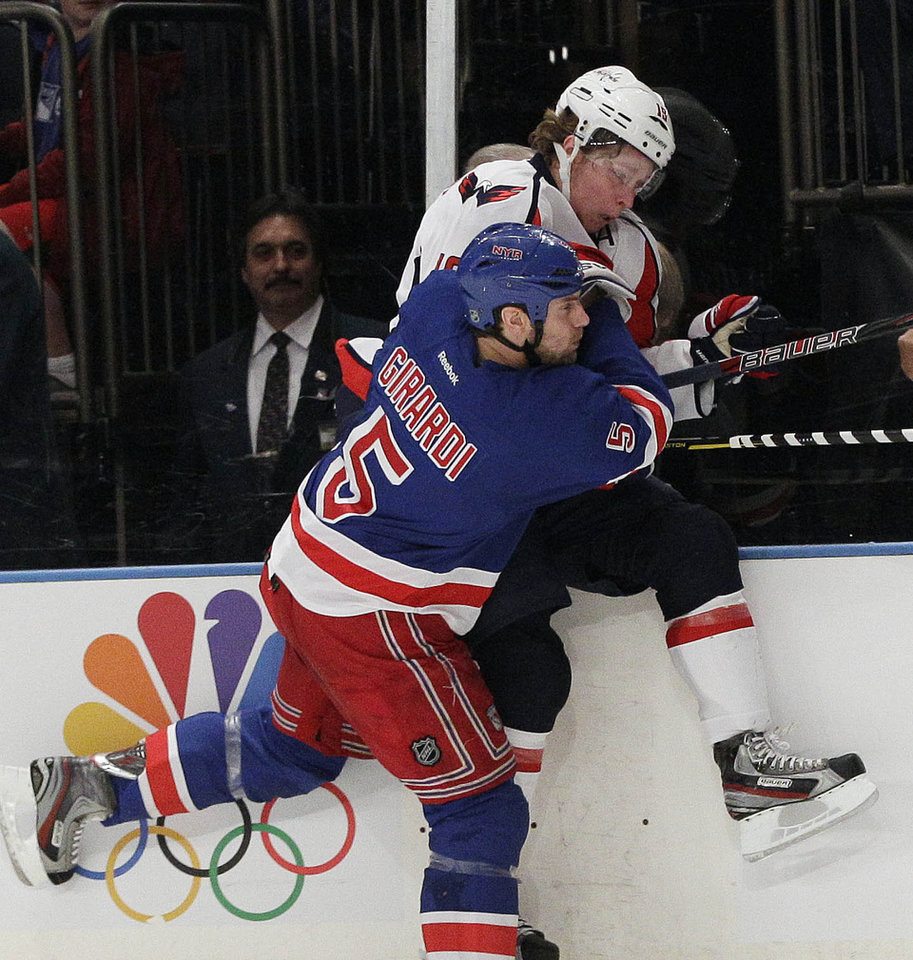 Photo -   New York Rangers' Dan Girardi (5) checks Washington Capitals' Nicklas Backstrom (19) during the first period of Game 1 in the second round of the NHL hockey Stanley Cup playoffs Saturday, April 28, 2012, in New York. (AP Photo/Frank Franklin II)