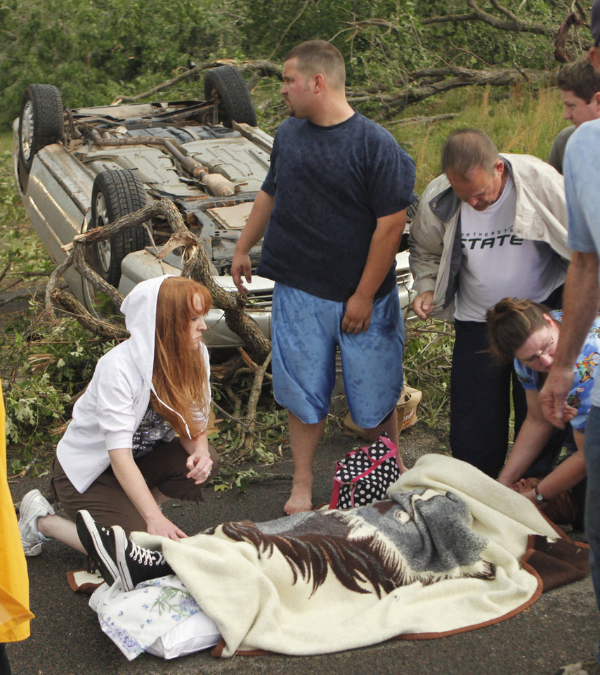 Photo - A woman injured on SE 84th street is attended to north of Highway 9 after a tornado touched down Monday, May 10, 2010, in Norman, Okla.  Photo by Steve Sisney, The Oklahoman