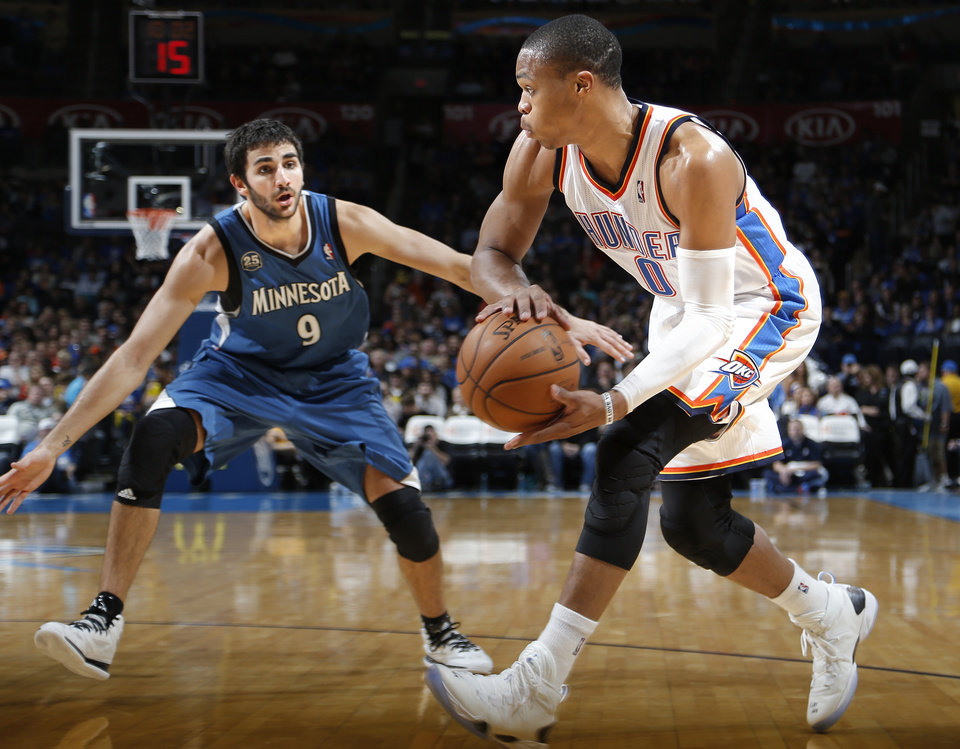 Photo - Oklahoma City's Russell Westbrook (0) passes the ball around Minnesota's Ricky Rubio (9) during the NBA game between the Oklahoma City Thunder and the Minnesota Timberwolves at the Chesapeake Energy Arena, Sunday, Dec. 1, 2013. Photo by Sarah Phipps, The Oklahoman
